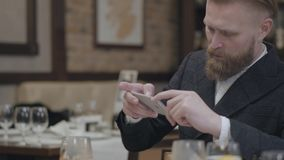 Confident blond bearded man in stylish jacket taking a photo of his food with his cellphone sitting in a modern. Confident blond bearded man in stylish jacket stock video
