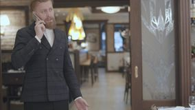 Confident blond bearded man in stylish jacket talking by cellphone standing in modern restaurant. The businessman. Confident blond bearded man in stylish jacket stock video footage