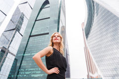 Confident blonde woman with arms akimbo on skyscraper background Stock Images