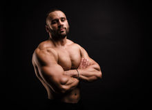 Confident bodybuilder on a black background. Sports man shirtless, with crossed hands. Athletic male model. Copy space. Stock Photos