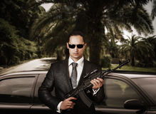 Confident bodyguard holding automatic. Royalty Free Stock Photography