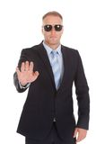 Confident bodyguard making stop gesture. Portrait of confident bodyguard making stop gesture over white background royalty free stock photos