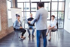 Confident boss leader coaching and teaching in modern office. On royalty free stock photography