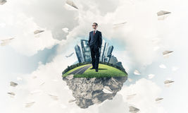Confident boss and modern city as concept of eco green construct. Elegant confident businessman standing on green floating island in blue sky royalty free illustration