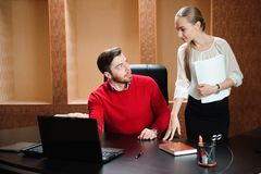 Confident boss with paper explaining something to secretary in the office. royalty free stock images