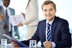 Confident boss. Portrait of confident boss looking at camera with his partners interacting on background Stock Image
