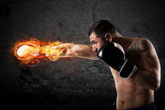 Confident boxer with fiery boxing gloves. Determined and confident boxer with fiery boxing gloves Stock Photo