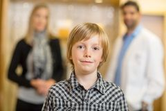 Confident Boy With Optometrist And Mother At Store Stock Image
