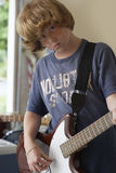 Confident Boy Playing Guitar In Garage Royalty Free Stock Photos