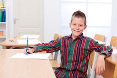 Confident boy sitting alone in classroom Stock Photo