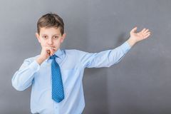 Confident boy student before dark background with copy-space. As a blackboard Royalty Free Stock Photography
