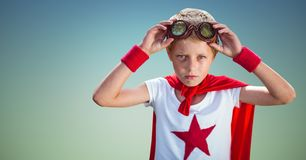 Confident boy wearing superhero costume standing against sky blue background. Portrait of confident boy wearing superhero costume standing against sky blue Royalty Free Stock Photography