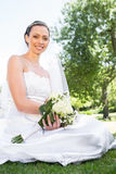 Confident bride holding bouquet in garden Stock Photo