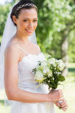 Confident bride holding flower bouquet in garden Stock Image