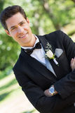 Confident bridegroom with arms crossed in garden Stock Photo