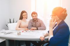 Confident Broker With Home Sellers Behind. Young family couple purchase rent property real estate . Agent giving. Consultation to men and woman. Signing Royalty Free Stock Images