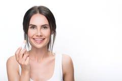 Confident brunette girl using lip gloss royalty free stock images