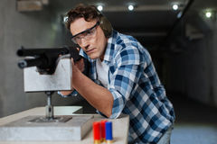 Confident brutal man wearing safety glasses. Protective eyewear. Confident brutal serious man wearing safety glasses and aiming at the target while using the Stock Image