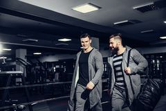 Confident young sportsmen leaving gym. Confident brutal men holding bags and leaving gym after workout looking forward Royalty Free Stock Photos