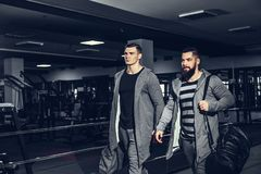 Confident young sportsmen leaving gym. Confident brutal men holding bags and leaving gym after workout looking forward Stock Images