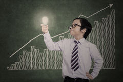 Confident business boy holding lit bulb on bar chart Royalty Free Stock Images