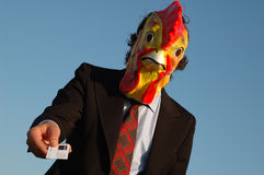 Confident business chicken with business card. Confident business man with chicken mask handing over his business card royalty free stock images