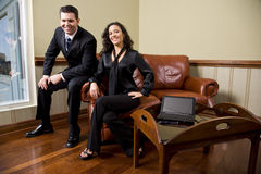 Confident business couple on sofa in office Royalty Free Stock Photos