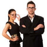 Confident business couple standing next to each other. Woman loo. King over the glasses and smiling. Conceptual image Royalty Free Stock Photography