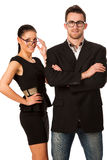 Confident business couple standing next to each other. Woman loo. King over the glasses and smiling. Conceptual image Royalty Free Stock Image