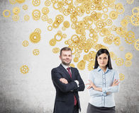 Confident business duo and gold gears Stock Image
