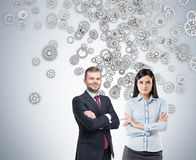 Confident business duo and silver gears Stock Photo