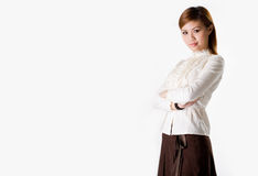 Confident business executive. Confident female business executive cross hand looking very approachable wearing a white blouse and dark brown skirt smiling Stock Image