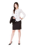 Confident business executive woman. Of Asian standing and holding her coat, full length portrait isolated on white background Stock Photo