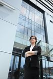 Confident business executive woman. Businesswoman with glasses and having arms crossed, standing in front of an office building skyscraper Stock Image