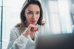 Confident business female using mobile laptop for looking a new business solution during work process at office.Blurred stock image