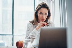 Confident business female using mobile laptop for looking a new business solution during work process at office.Blurred royalty free stock images