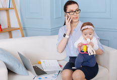 Confident business lady negotiating a new deal. Can do both. Professional active classy women managing taking care of her child and doing business while spending Stock Photos