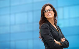 Confident business leader. Businesswoman in leadership confident pose outside corporate building. Business woman crossing arms and smiling Stock Photography