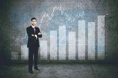 Confident business leader with finance graph Stock Photo