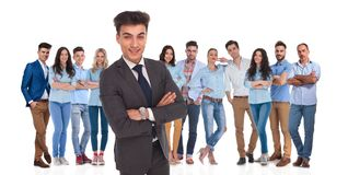 Confident business leader standing in front of his casual team. Confident business group leader standing in front of his young casual team with crossed hands on royalty free stock photos