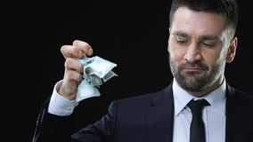 Confident business man clenching and throwing dollar banknotes, life values. Stock footage stock video
