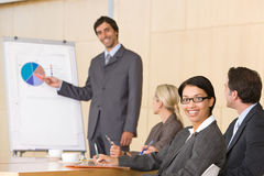 Confident business man giving presentation. To colleagues in a boardroom Royalty Free Stock Images