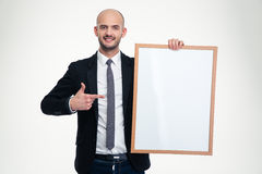 Confident business man holding blank board and pointing on it Royalty Free Stock Photography