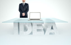 Confident business man leaning on empty glass table with a base made of concrete IDEA. Business concept Stock Images