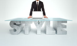 Confident business man leaning on empty glass table with a base made of concrete STYLE. Business concept Stock Photos