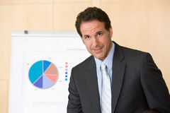Confident business man with report in background Royalty Free Stock Image