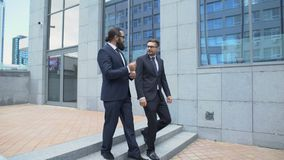 Confident business partners exiting from office building and communicating stock footage