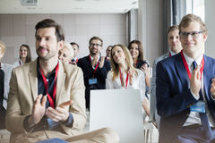 Confident business people applauding during seminar.  Royalty Free Stock Images