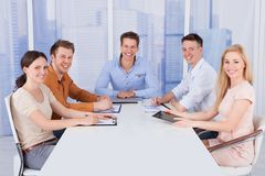 Confident Business People At Conference Table In Office Stock Photo