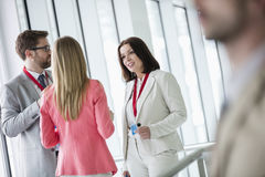 Confident business people discussing in brightly lit convention center Stock Photo